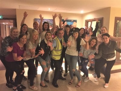 a large hen party posing with jazz hands