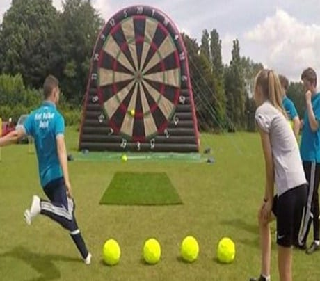 2 men taking wearing football gear taking football shots at a large dart board