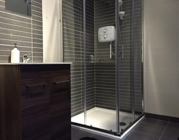 a shower with grey tiles in one of our hen party apartments in carrick on shannon