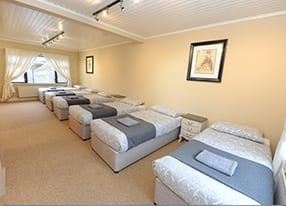 a bedroom with 6 single beds with grey throws