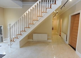 a white staircase in a hall with cream tiles